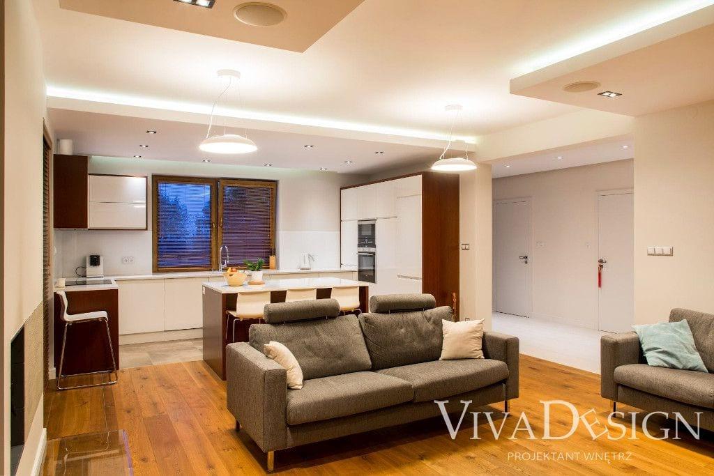 Nowoczesna jasna kuchnia z drewnem, widok z salonu - Viva Design