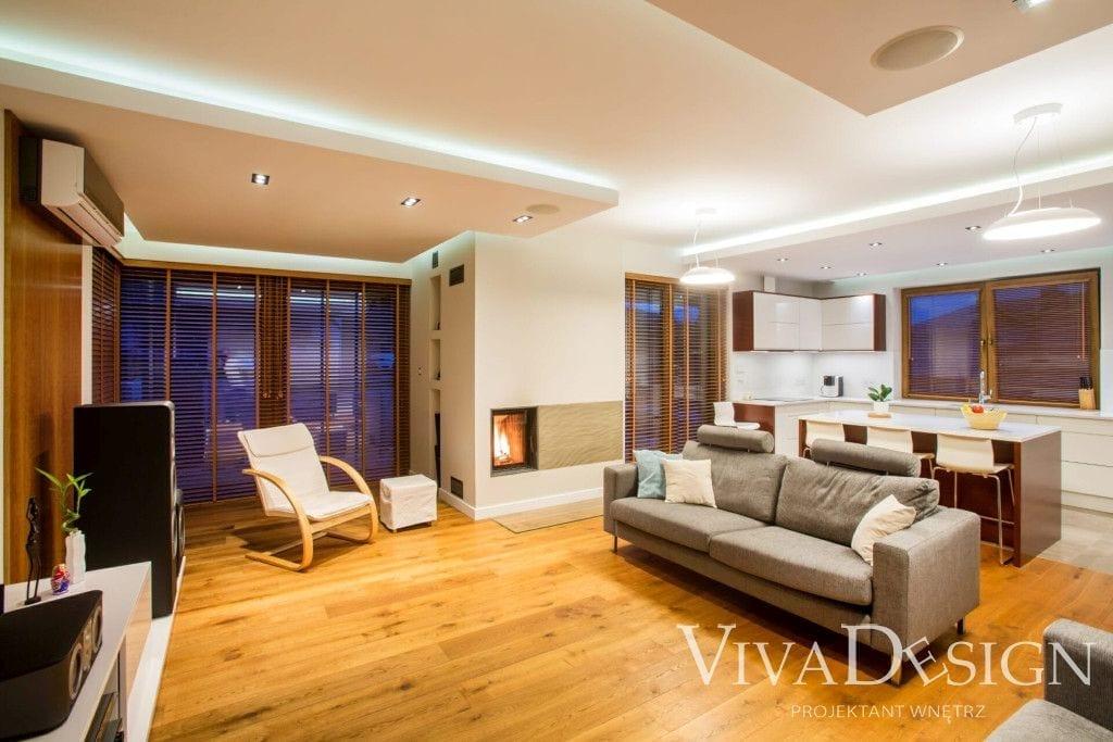 Rozświetlony dom jasna podłoga beżowa sofa kominek