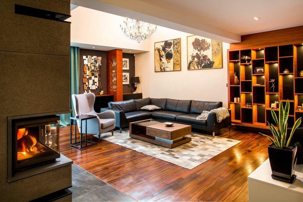 Luksusowo urządzony salon z kominkiem, antresolą, sofą, betonem, regałem - Viva Design