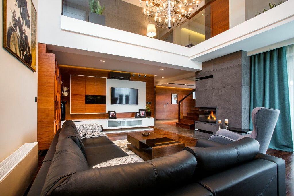 Luksusowy salon, kominek, beton, drewno, żyrandol, antresola, sofa - Viva Design