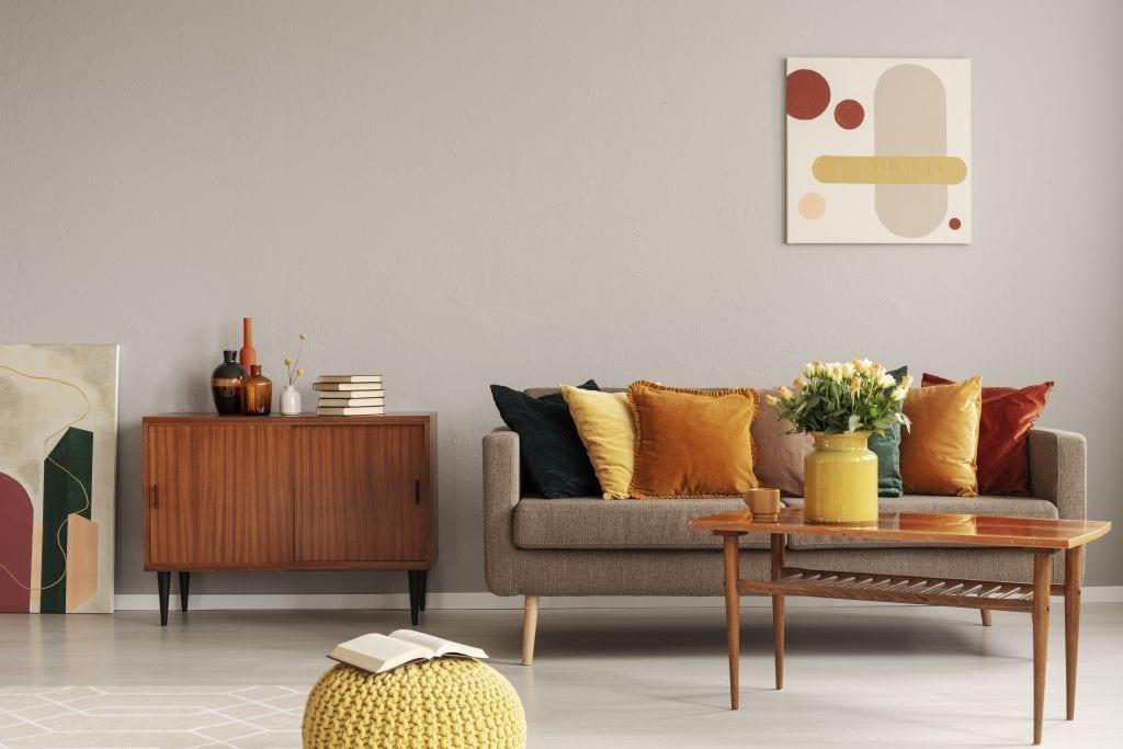 styl vintage wnętrze beżowe żółte dodatki pomarańczowe poduszki komódka politura